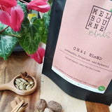 Authentic Chai Spices powder blend, Vegan, Caffeine Free, Lactose Free, Gluten Free, packed in 200gr black bag with pink label position on timber board