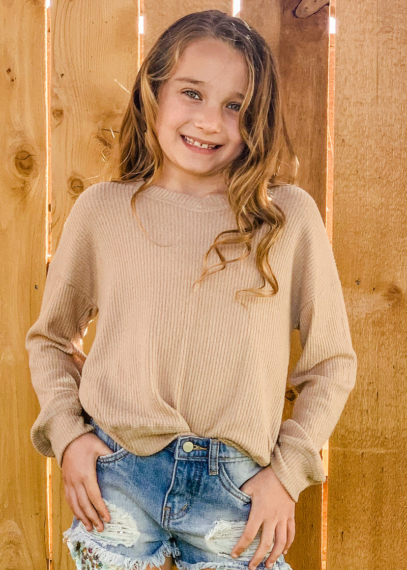Little girl in our camel colored rib long sleeve top.