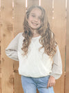 Little girl in our cream, ribbed balloon sleeve top.
