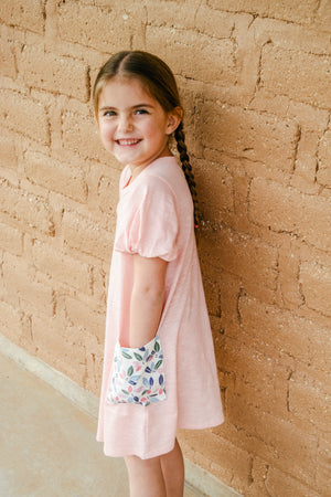 Little girl in our pink floral pocket dress.
