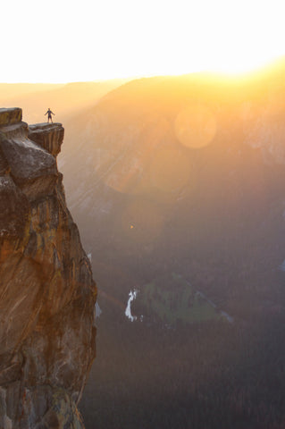 man standing on cliff's edge during sunrise ready to seize the day