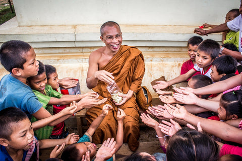 Kind monk giving out to children