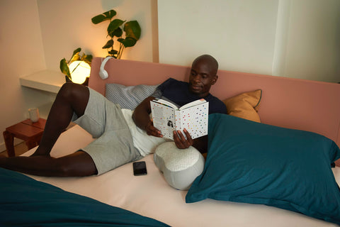 Man reads book to relax before sleeping
