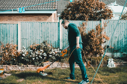Man using a hose to water plants in the garden