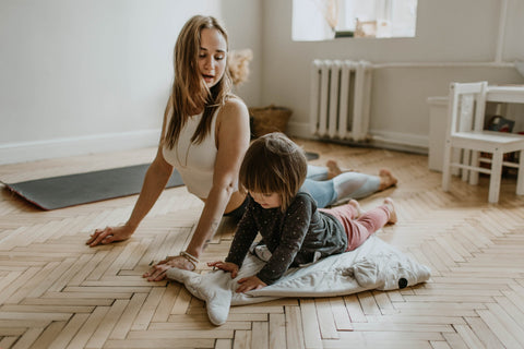 Mom doing yoga with daughter at home