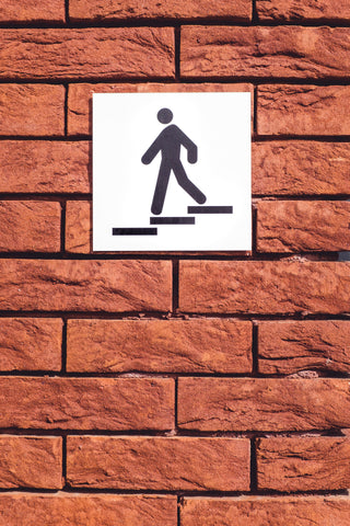 Walking sign posted on brick wall
