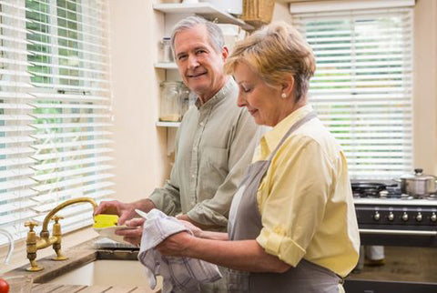 mature couple washing dish with water