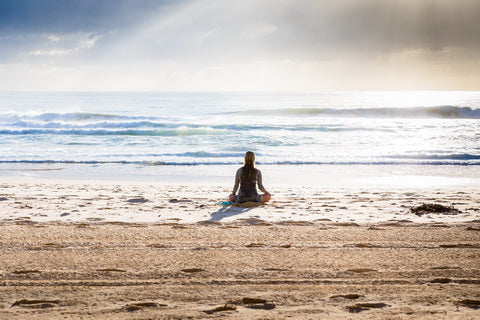 woman meditating by the beach