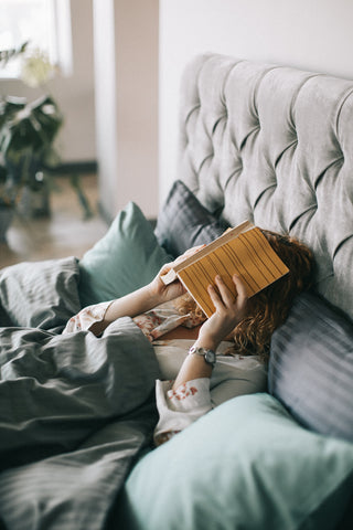 woman covering face with book in bed