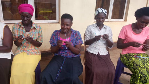 The women rolling the paper into beads