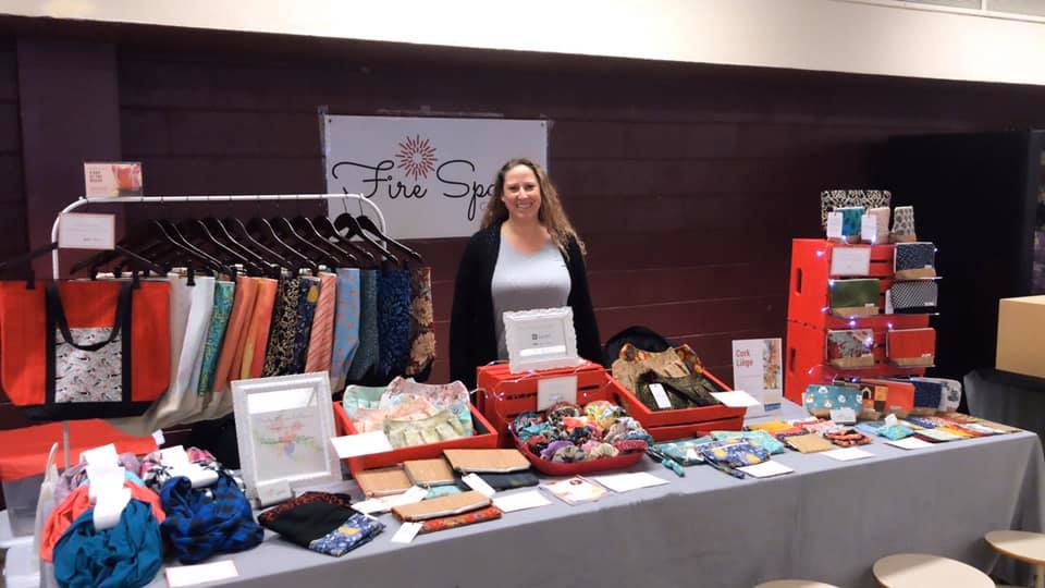 Lisa Sparkes of Fire Sparks Creations standing behind tables with tote bags, handbags, accessories, and infinity scarves at a craft show