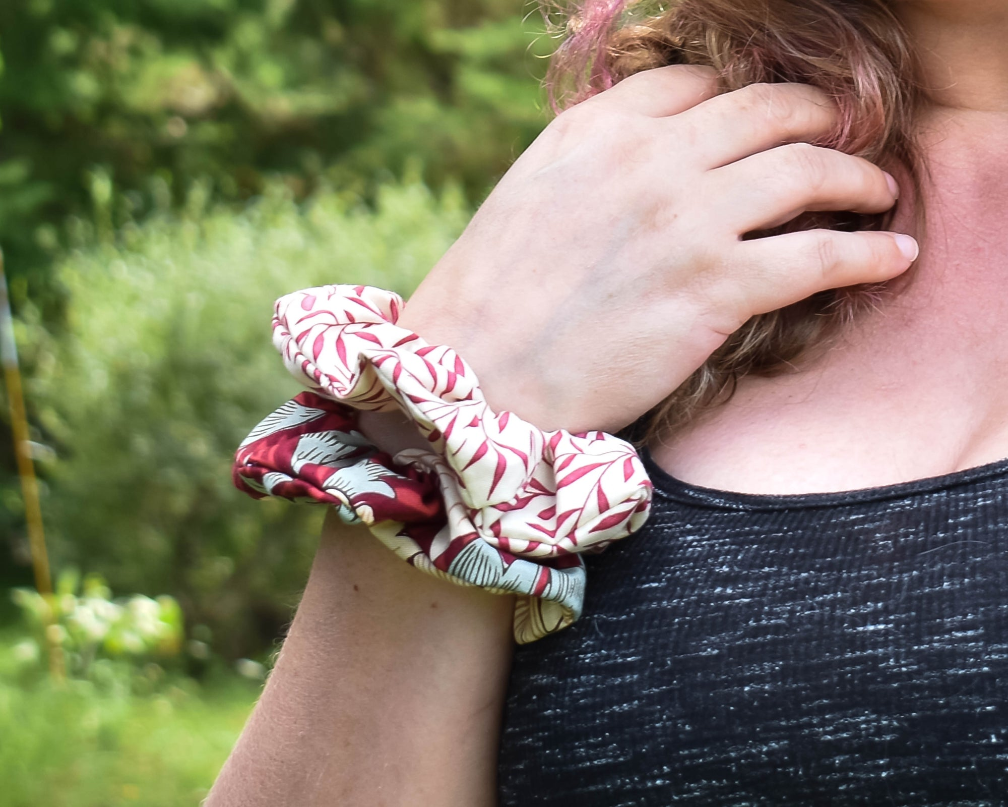 A red scrunchie, and a cream and red scrunchie are on the wrist of Lisa Sparkes of Fire Sparks Creations