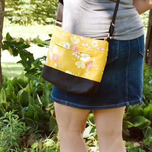 Woman wearing yellow floral and black cross body bag