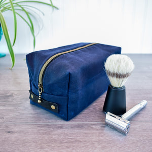 A steel grey dopp kit toiletry bag with antique brass zipper and rivets, and black leather handle, sits on a bathroom counter with a green plant and soap dish in the background.