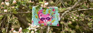 A raccoon coin purse from Fire Sparks Creations sits on a branch in an apple tree with apple blossoms