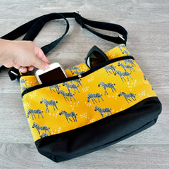 Zebra cross body bag with sunglasses and cell phone peeking out of pockets