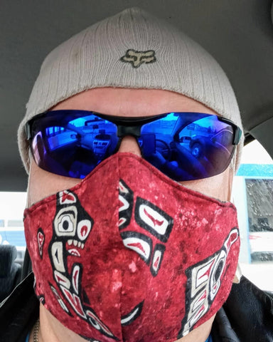 man with sunglasses and hat wearing a red non-medical face mask with west-coast Indigenous designs