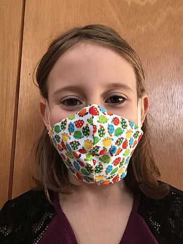 young girl wearing non-medical face mask with multicolour turtle print