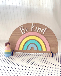 Wooden freestanding rainbow with pastel acrylic and the words Be Kind