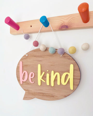Wooden speech bubble plaque with yellow and pink acrylic letters which say be kind