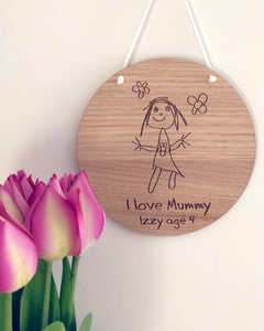 children's drawing engraved into a circular wooden plaque