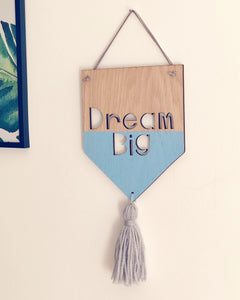 Wooden banner with Dream Big laser cut out, hand painted in blue and grey woollen tassel attached