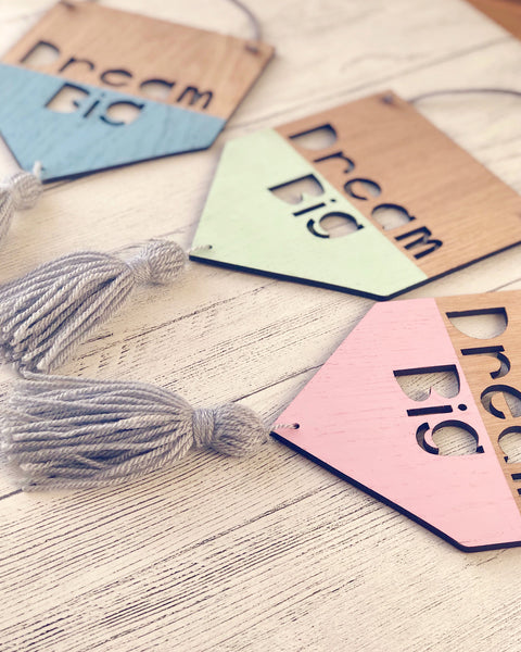Wooden banners with Dream Big laser cut out, hand painted in blue, green and pink and grey woollen tassel attached