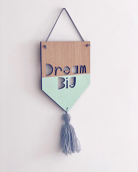 Wooden banner with Dream Big laser cut out, hand painted in mint green and grey woollen tassel attached
