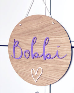 circular wooden plaque with personalised name cut from lilac acrylic and a white acrylic heart
