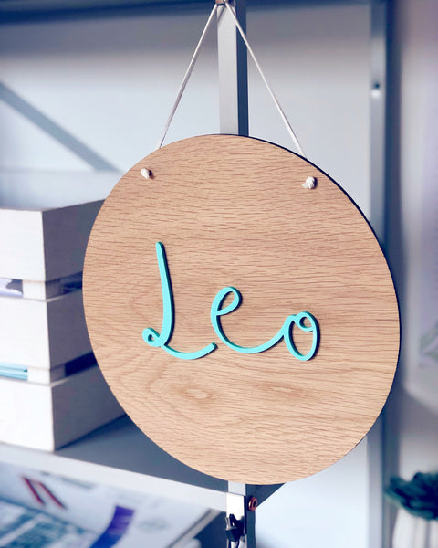 circular wooden plaque with personalised name cut from mint green acrylic