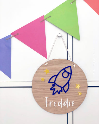wooden plaque with acrylic blue rocket and yellow stars. Personlised with a name in white acrylic letters