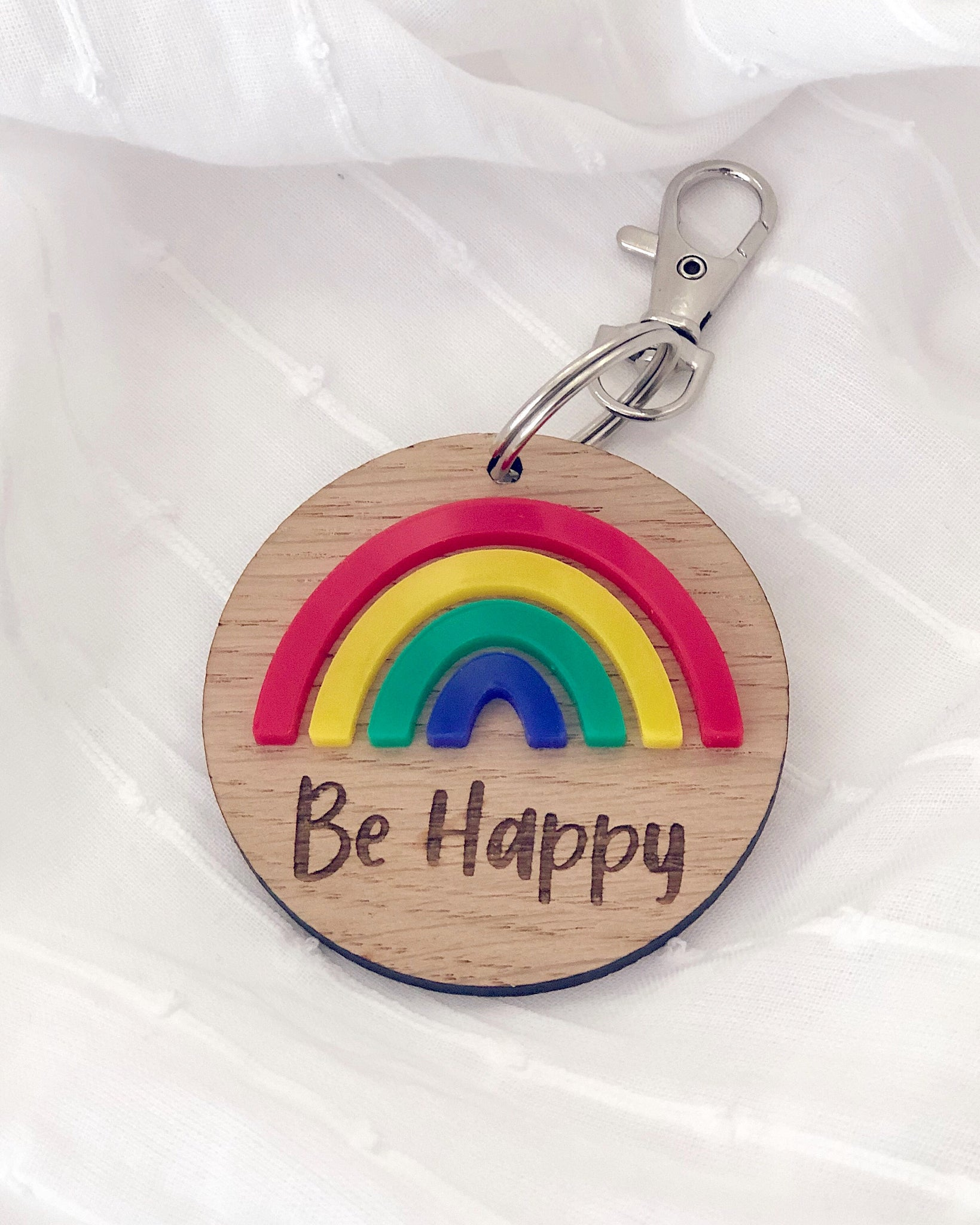 Wooden key ring with colourful rainbow and be happy engraved text