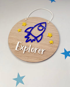 Wooden plaque with blue rocket and yellow stars. With the word Explorer written on