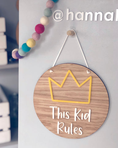 wooden plaque with acrylic yellow crown and This Kid Rules text in white acrylic