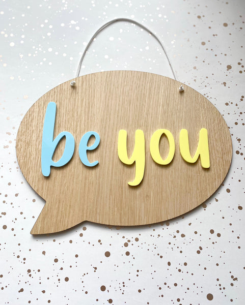wooden hanging plaque in the shape of a speech bubble with be you in mint green and lemon yellow acrylic