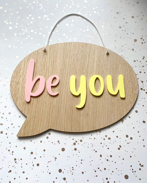 wooden hanging plaque in the shape of a speech bubble with be you in pastel pink and lemon yellow acrylic