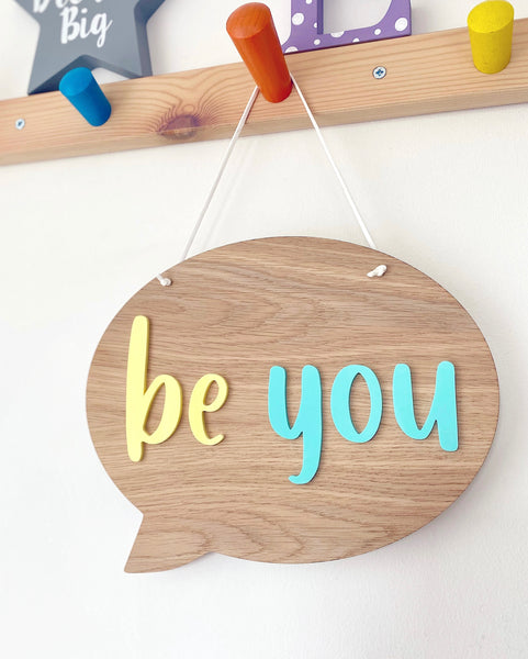 wooden hanging plaque in the shape of a speech bubble with be cool in lemon yellow and mint green acrylic