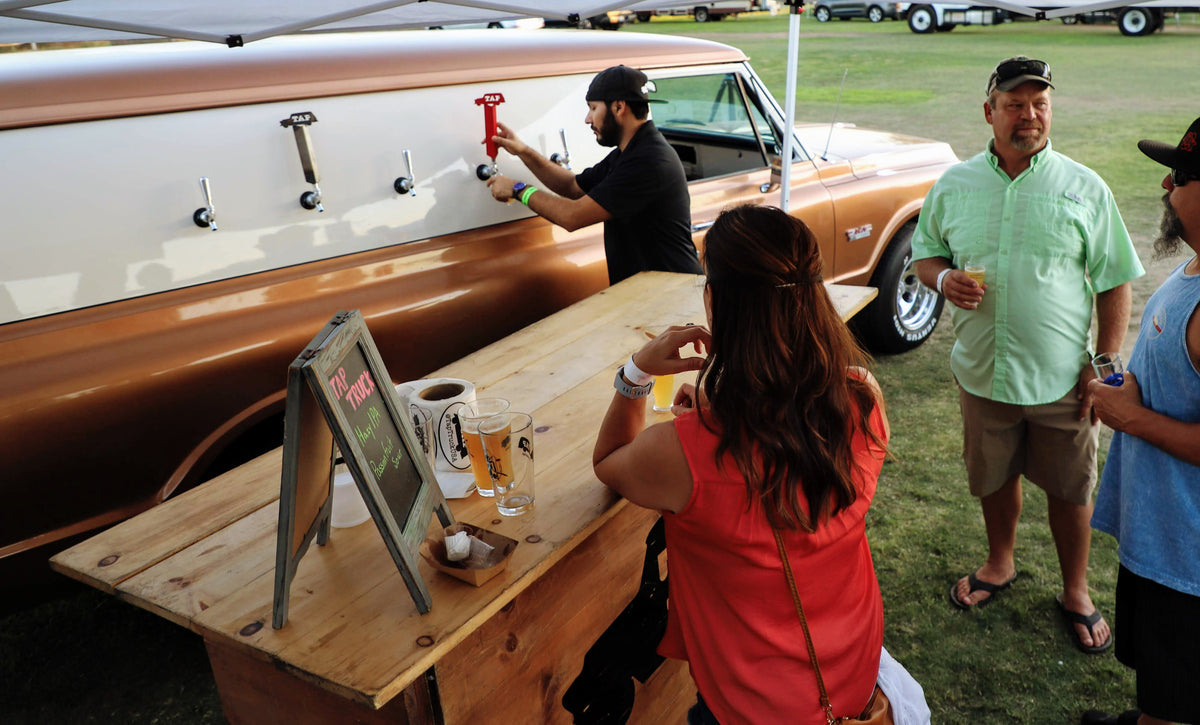 Beer festival serving up ice cold beverages via a tap truck. The beer truck in the form of a 1969 gmc panel truck