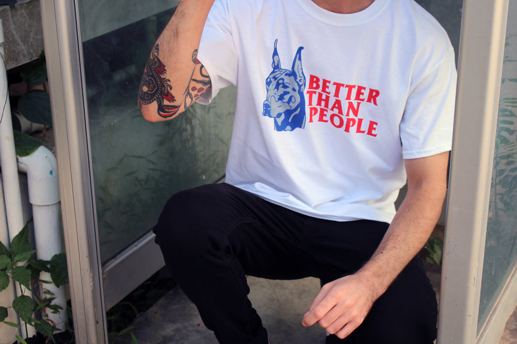 Caucasian male model wearing streetwear brand Meaningless Ritual t-shirt featuring a doberman and text Better Than People
