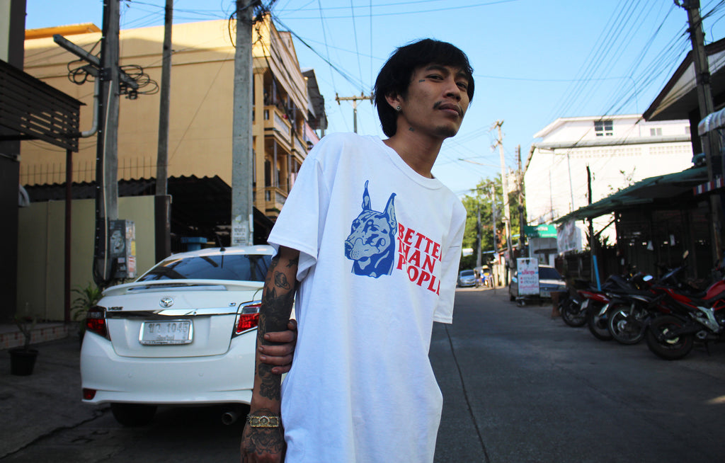 Asian model wearing streetwear brand Meaningless Ritual t-shirt featuring a doberman and the text Better Than People