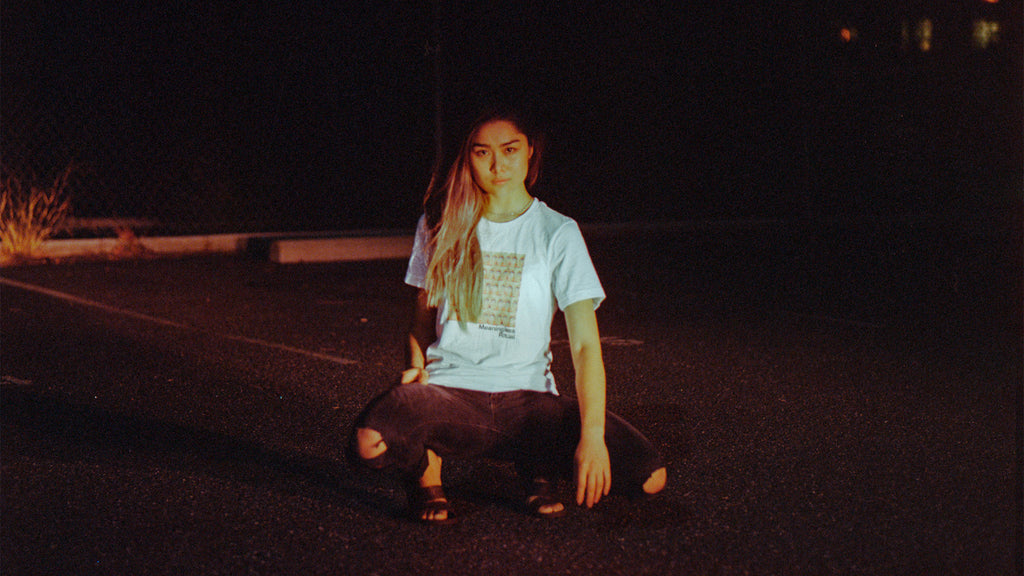 Night shot of asian model wearing streetwear brand Meaningless Ritual, a white shirt featuring a psychedelic repeating vintage image of a Caucasian woman's eyes