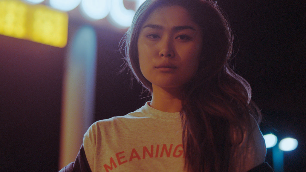 Night time film shot of asian female model wearing streetwear brand Meaningless Ritual heather ash shirt with red type that simply says MEANINGLESS