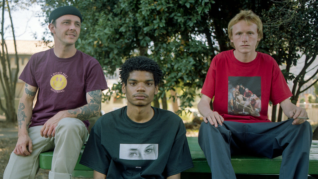 Group shot of male models wearing streetwear brand Meaningless Ritual shirts, including an ironic I Don't Feel Anything smiley face design, a shirt with a minimal monochrome image of a woman's eyes, and collage art featuring Renaissance art of jesus and marijuana