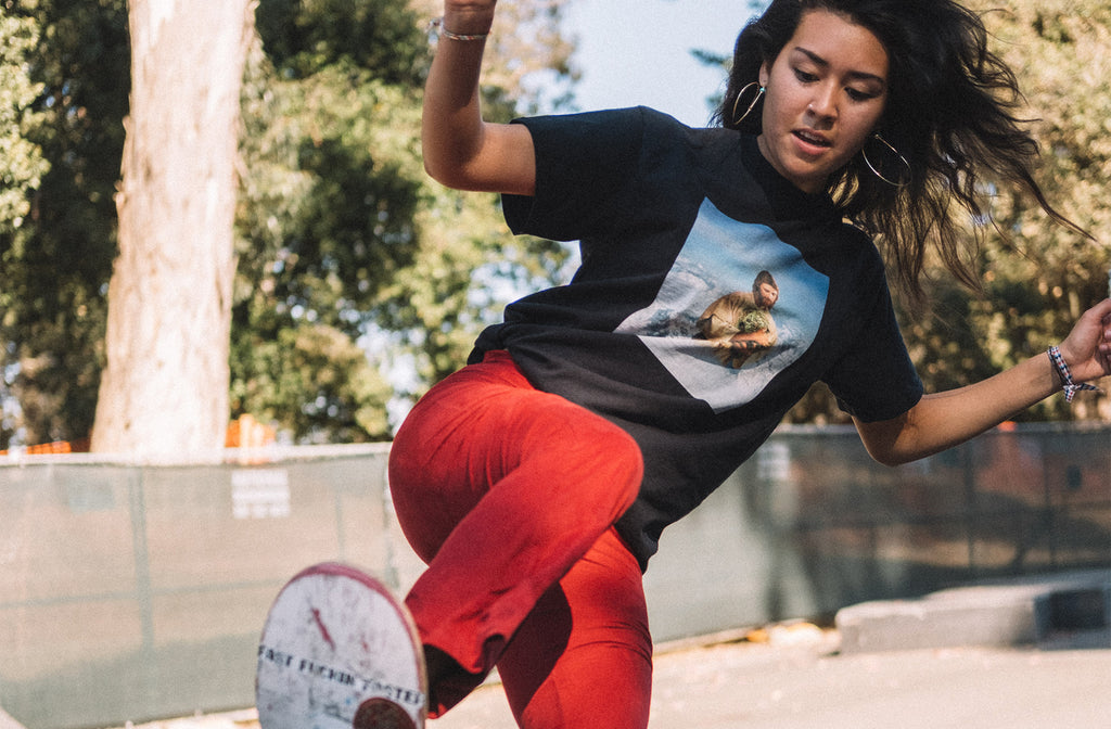 Outdoor shot of female skater model skating and wearing streetwear brand Meaningless Ritual black shirt featuring collage artwork of a mountain sized Jesus holding a giant nug of weed