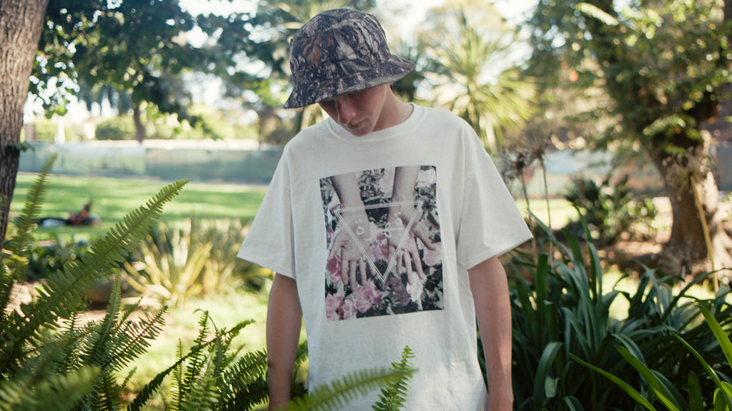 Outdoor shot of white male model wearing streetwear brand Meaningless Ritual white shirt featuring collage artwork of flowers, hands, geometric shapes, and arabic text.