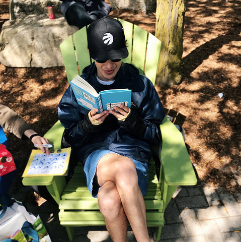 Young adult reading book outside on an Adirondack chair