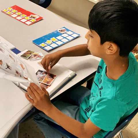 Boy sitting down at a table while observing a folder of learning material