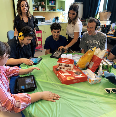 Adults around a table playing on tablets and getting ready to eat