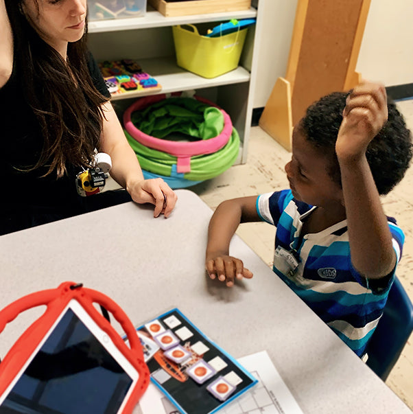New Haven Team Member sitting with young boy while interacting with learning material