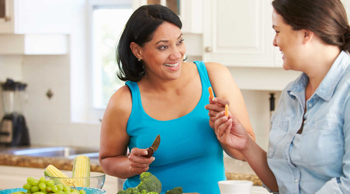 two women talking while preparing a meal